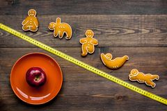Yoga und gesunde Diät für verlieren Gewicht Platte, Apfel, messendes Band und Plätzchen in Form von Yoga asans auf dunklem hölzer lizenzfreies stockfoto