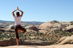 Yoga up-high. Picture of a woman who do the tree pose in a yoga practice at the top of a mesa in Utah near Moab Stock Image