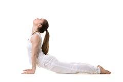Yoga upward facing dog pose. Young fitness model in white sportswear doing yoga or pilates training, urdhva mukha shvanasana (upward facing dog pose), side view Royalty Free Stock Image