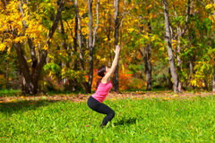 Yoga utkatasana pose. Woman exercises in the autumn forest yoga utkatasana pose Royalty Free Stock Photography
