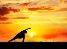 Yoga utthita parsvakonasana pose. Yoga utthita parsvakonasana horizon pose by man silhouette at sunset sky background. Free space for text and can be used as Royalty Free Stock Photography