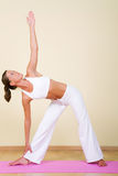 Yoga - Utthita Trikonasana. Young woman in a yoga position (Utthita Trikonasana Royalty Free Stock Image
