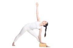 Yoga Utthita Trikonasana Pose with props. Sporty beautiful young beginning yoga female student standing in Utthita Trikonasana, Extended Triangle Pose with Royalty Free Stock Photos