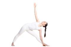 Yoga Utthita Trikonasana Pose. Sporty beautiful smiling young woman standing in Utthita Trikonasana, Extended Triangle Pose, studio full length profile view on Stock Photos