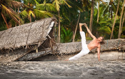 Yoga vasisthasana side plank pose. By fit man in white trousers on the beach near the fishermen boats in Varkala, Kerala, India royalty free stock photo
