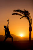 Yoga Viparita Virabhadrasana in tropical location. Silhouette of young woman doing lunge exercises, fitness, yoga or pilates training, standing in Reverse stock photography