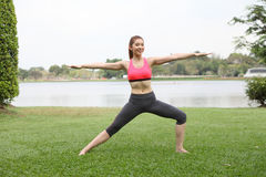 Yoga virabhadrasana II warrior pose by woman on lawn Stock Photo