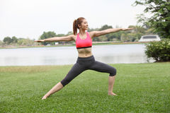 Yoga virabhadrasana II warrior pose by woman on lawn,right side Royalty Free Stock Image