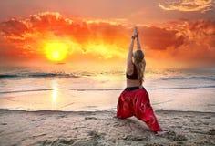 Yoga virabhadrasana warrior pose at sunset. Beautiful woman doing virabhadrasana I, warrior yoga pose on the beach near the ocean at sunset in India Royalty Free Stock Photo