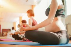 Yoga voor zwangere vrouwen Jong mooi zwanger meisje in sportkleding die yoga in de gymnastiek doen stock foto's