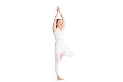 Yoga Vriksasana pose. Sporty attractive young woman in white sportswear doing yoga Tree pose, hands above the head in Anjali mudra, part of large photo series Royalty Free Stock Photography