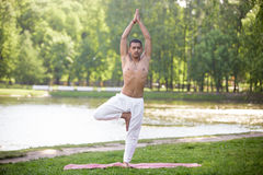 Yoga Vrikshasana pose. Serene attractive Indian young man in white linen clothes working out on riverbank in park, standing in Vrikshasana (Vriksasana, Tree Pose Stock Images