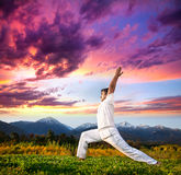 Yoga warrior pose in mountains Royalty Free Stock Photo