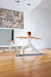 Yoga Warrior two II pose in wooden floor Royalty Free Stock Photo