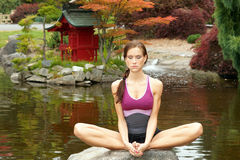 Yoga woman relaxes rock Pagoda pond Royalty Free Stock Images
