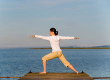 Yoga Woman. On a dock by the ocean Stock Image