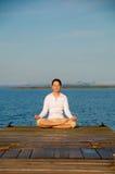 Yoga Woman. On a dock by the ocean stock photos