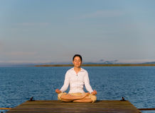 Yoga Woman. On a dock by the ocean stock photography