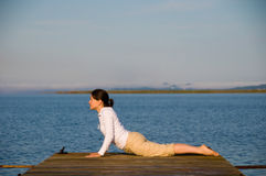 Yoga Woman. On a dock by the ocean Stock Photo