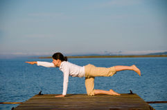 Yoga Woman. On a dock by the ocean royalty free stock images