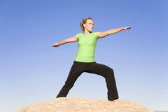 Yoga woman arms out. A woman on a rock with a blue sky doing the warrior two yoga move Royalty Free Stock Photos
