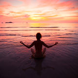 Yoga woman on the beach Stock Photos