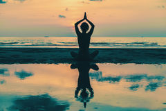 Yoga. Woman on the beach with reflection in water. Stock Photos