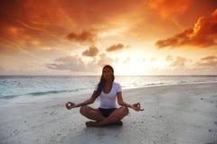 Yoga woman on beach at sunset Stock Photos