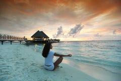 Yoga woman on beach at sunset Royalty Free Stock Photos