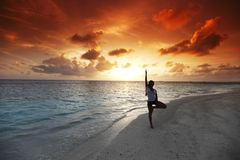 Yoga woman on beach at sunset Stock Photo