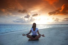 Yoga woman on beach at sunset Stock Photography