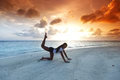 Yoga woman on beach at sunset Royalty Free Stock Images