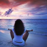 Yoga woman on beach at sunset Royalty Free Stock Image