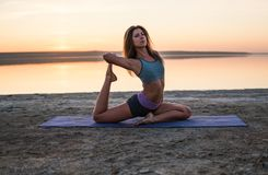 Yoga woman on the beach at sunset. Stock Images