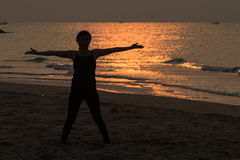 Yoga woman on the beautiful beach at sunrise Stock Image