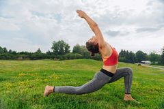 Yoga woman performing sun salutation on warm summer morning. Yoga woman. Beautiful slim and healthy yoga woman performing sun salutation on warm summer morning royalty free stock photos