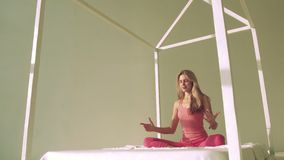 Yoga woman in bed meditating in lotus pose stock video footage
