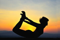Yoga. Woman doing yoga at sunset Royalty Free Stock Photos