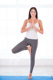 Yoga woman doing tree pose Stock Photo