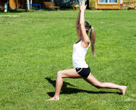Yoga woman on green grass. Young woman is engaged in yoga, in summer on a green grass Stock Photos