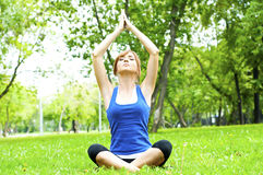 Yoga woman on green grass. Young woman is engaged in yoga, in summer on a green grass Stock Photo