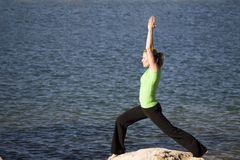 Yoga woman hands up by water. A woman doing yoga position warrior one while standing on a rock by the water Stock Images