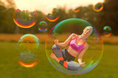 A yoga woman is hovering. In a soap bubble Royalty Free Stock Photo