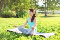 Yoga woman meditates on grass pose lotus in summer Royalty Free Stock Image