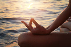 Yoga woman meditatiing in lotus pose on the beach during sunset Stock Photos