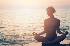 Yoga woman meditating in lotus pose on the beach during sunset Royalty Free Stock Photography