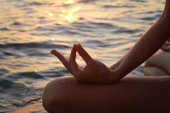 Yoga woman meditating in lotus pose on the beach during sunset Royalty Free Stock Image