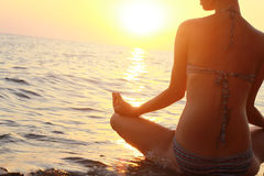 Yoga woman meditating in lotus pose on the beach during sunset Stock Image