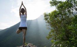 Yoga woman meditating on mountain peak cliff edge stock photos