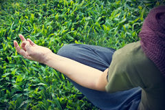 Yoga woman meditating outdoor in park on grass field background, Focus on hand, Top view Stock Photo